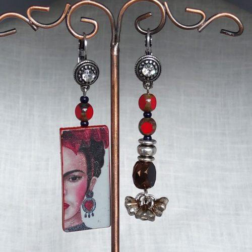 Boucles d'oreillesà l'effigie de Frida Kahlo. Montée sur d'une perle en verre, pour la deuxième perles en verre et apprêt fantaisie. Le tout montées sur dormeuse acier surplombées d'une perle en verre. Couleurs dominantes rouge et noir, hauteur 6,5 cm, largeur 1,7 cm.