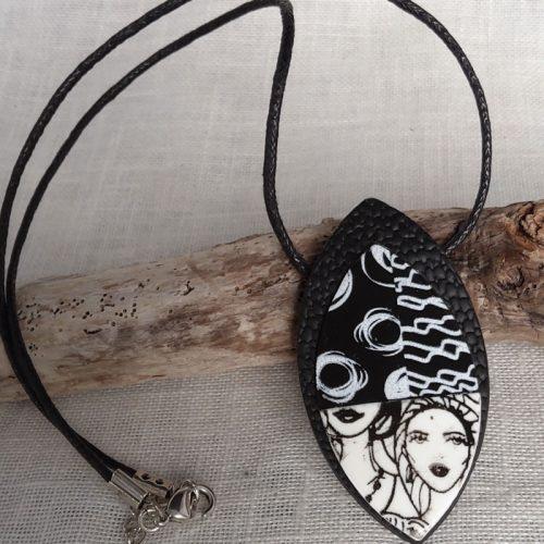 Collier de forme ovale, effet cuir, motif personnage, couleur noir et blanc. Monté sur cordon en coton, longueur 46 cm et rallonge de 6 cm.