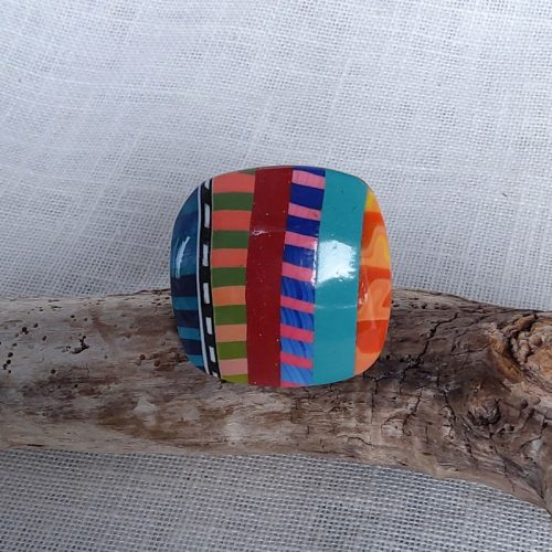 Bague de couleur multicolore.. Montée sur support réglable en métal argenté. Taille 3cm sur 3cm.