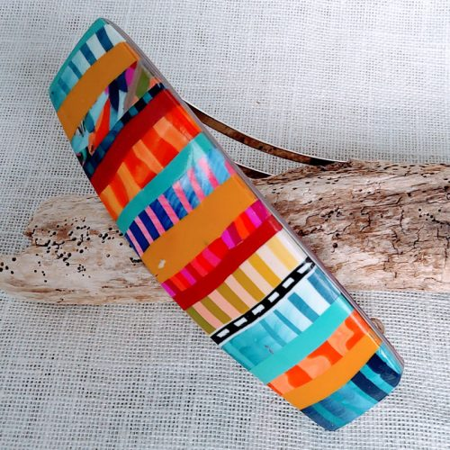 Barrette de couleur multicolore, longueur 7,8 cm, largeur 2,8 cm. Montée sur support en métal argenté.